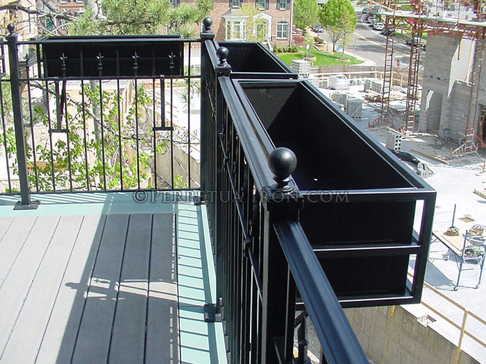 A fabricated steel flower box hanging on a balcony railing.