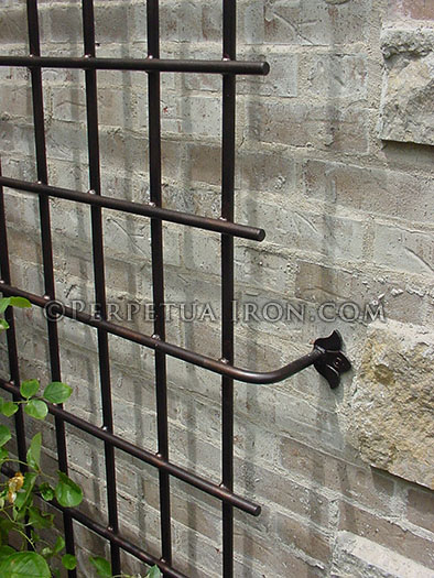 Detail of decorative iron trellis mounting point on a stone wall.