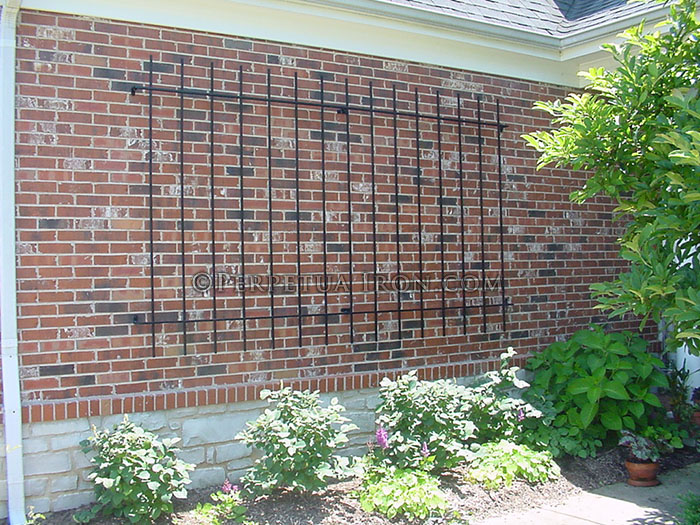 custom fabricated, simple, rectangular garden trellis mounted to a brick wall.