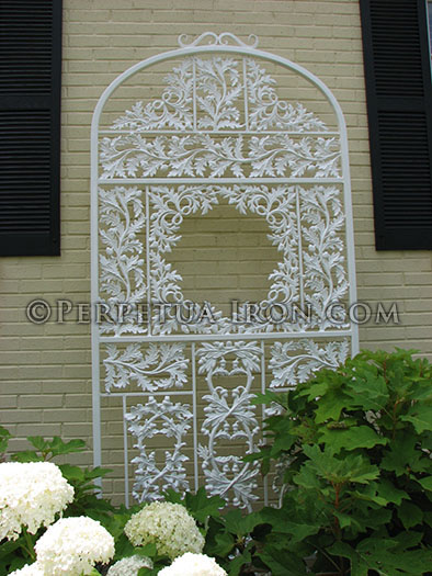 Ornate, white, decorative iron garden trellis against a pale yellow wall.