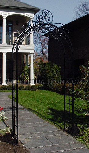 A black heavy duty decorative arched steel and iron trellis over a sidewalk
