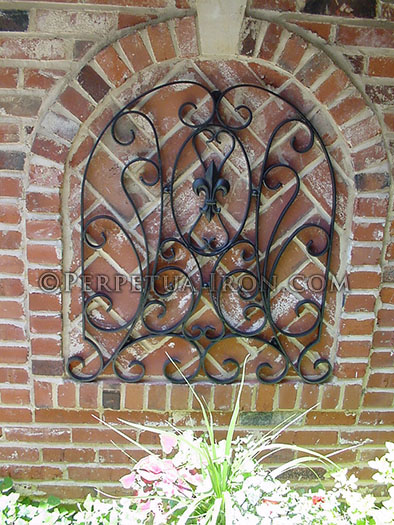 a wrought iron decorative panel that is formed to fit an arched brick wall detail