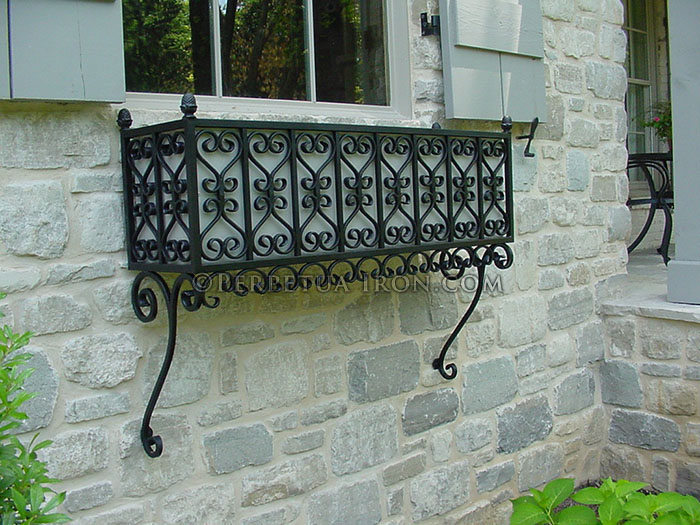 A high density scrolling designed black steel window box mounted below a window on a stone house. There are traditional painted gray shutters and muntined windows.