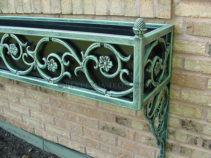 a wrought iron window boxlcose up detail showing a copper oxide patina and swirled flower design.