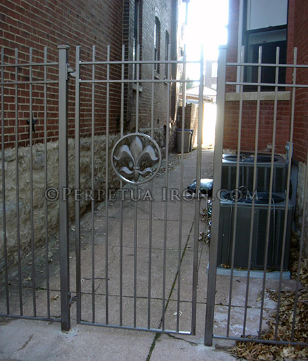 simple iron gate and panels with fleur de lis medallion between two old stone and brick houses.