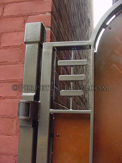 Heavy duty self closing hinges on a custom gate where the hinge is mounted to the front on a square post in front of an old bringk building instead of mounting it to the building.