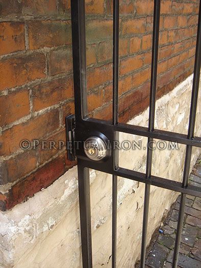 Chrome deadbolt lock in a simple garden on an old brick and stone building.