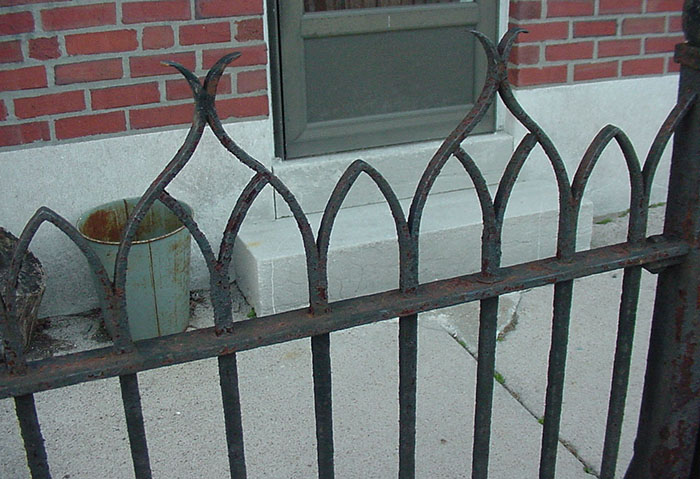detail of 4.1, old railing in front of a house.