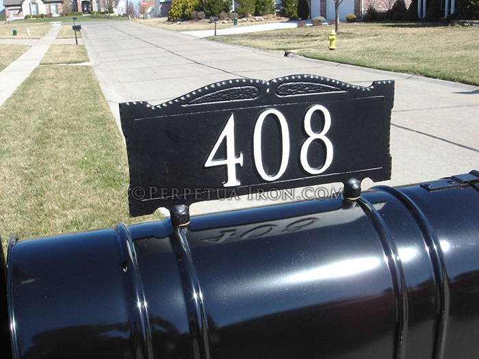 Address sign mounted on top of mailbox.