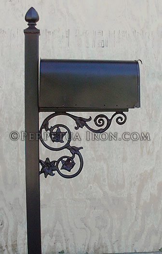 side view of a mailbox & post with cast iron support bracket and finial.