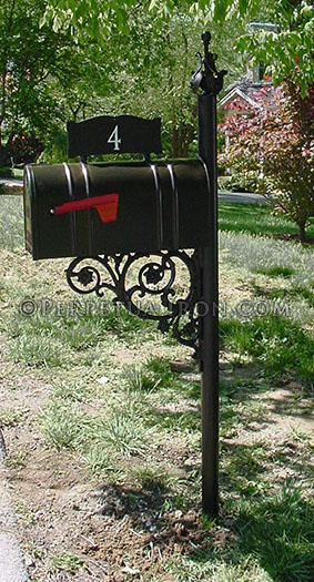 Mailbox in a grassy area with red flag down and the number 4 on a plate above the box.