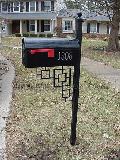 black mailbox in front of a house with a repeating square patterned finial
