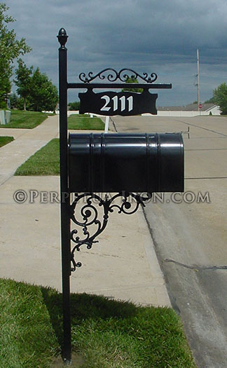 an ornamental iron mailbox post, with cast iron brackets for a sign that hangs over the box.