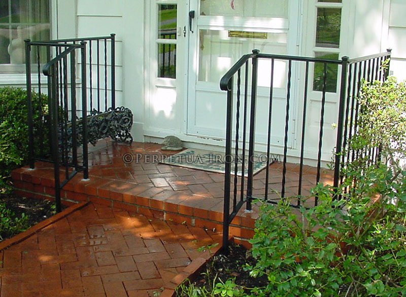 Wrought iron porch railing, design is alternating twisted pickets.