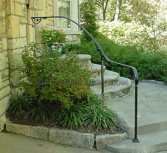 Flowing wrought iron handrail only, curved on site, with cast iron scrolls.