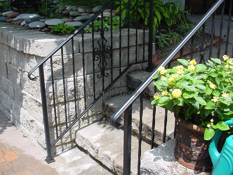 Wrought iron  railing for steps with twisted pickets and cast iron elements.