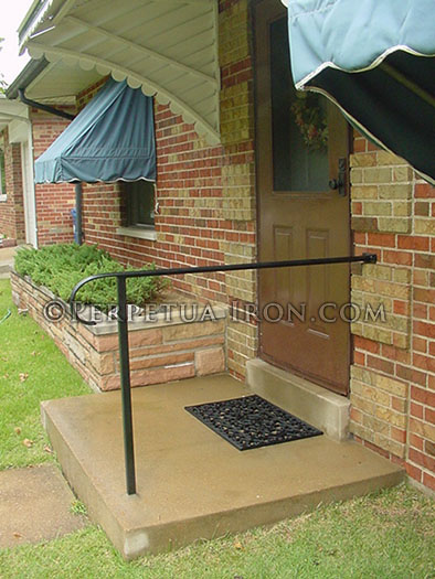 Wrought iron handrail and post for simple porch.
