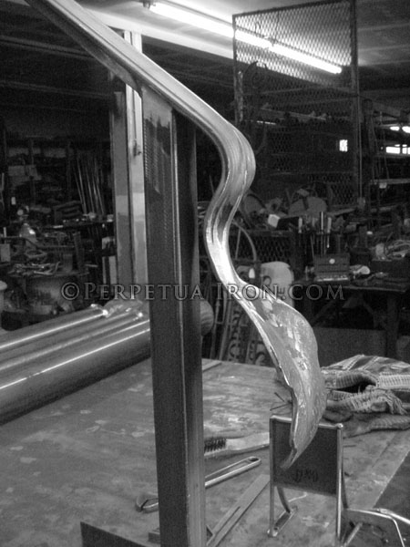Black and white image of a hand forged leaf shaped rail end.
