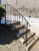 Exterior wrought iron handrail, curved, traditional design.