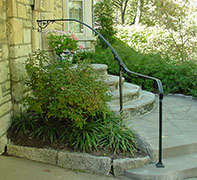 flowing wrought iron handrail only, curved on site, with cast iron scrolls
