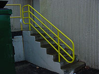 Bright yellow paint on a heavy industrial handrail on concrete steps for a loading dock.