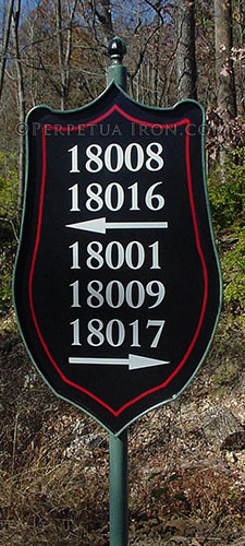 Custom made iron sign for a subdivision post painted green, sheild inspired shape painted black with red pinstripe line and white numbers with awwors pointing left and right.