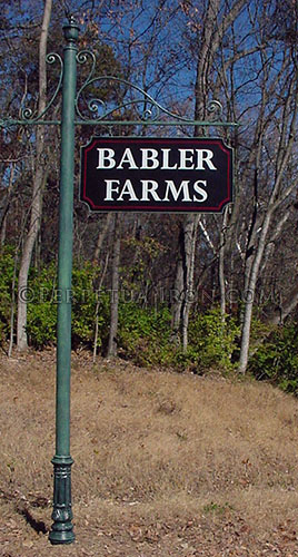 Large sign for a subdivision with green post, black sign with the word BABLER FARMS in white letters.