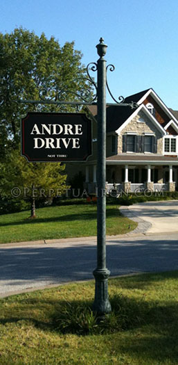 This iron street sign for a subdivision has hand made scrolls and a cast iron base. It reads Andre Drive.